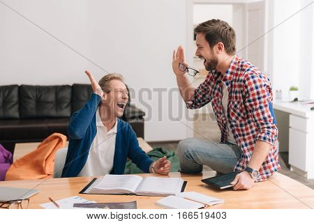 Good friends. Happy delighted positive men giving each other a high five and laughing while being in the great mood