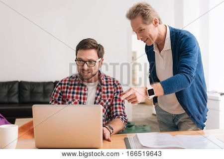 Giving advice. Handsome pleasant grey haired man standing and pointing at the laptop while giving advice to his younger colleague