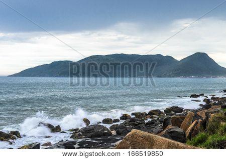 Water sea waves splashing on sea rocks on sea shore and a mountain on the background. Long exposure photo at Morro das Pedras Florianopolis Brazil.