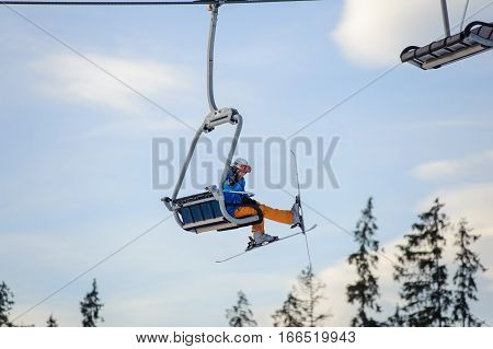 Skier Sitting At Ski Lift Against Blue Sky