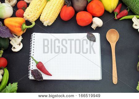 papaer with wooden spoon, on a black background with fresh vegetables