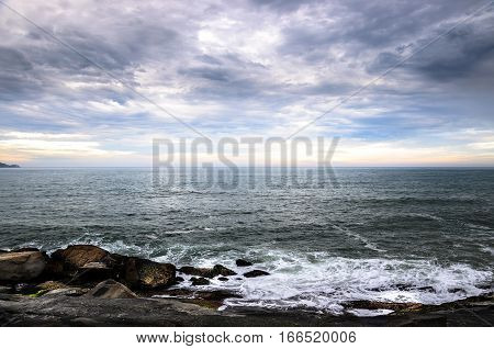 Large Rocks, Many Clouds, And The Horizon On A Seascape