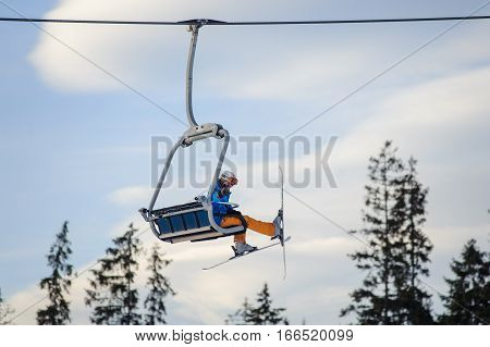 Skier Sitting At Ski Lift Against Blue Sky