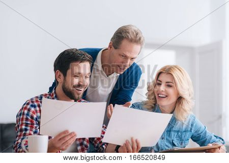 What do you think about this. Handsome nice delighted man standing behind his colleagues and pointing at the sheet of paper while discussing work issues with them