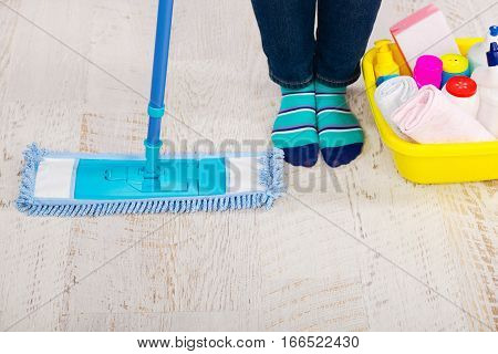 Bucket with many colorful detergent, mop and female legs close-up . Concept professional cleaning, top view
