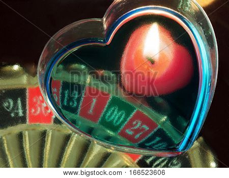 burning candle heart and a roulette wheel