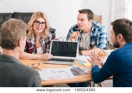 I want to present you something. Beautiful delighted young woman sitting at the table and pressing a button while showing something to her colleagues on the laptop