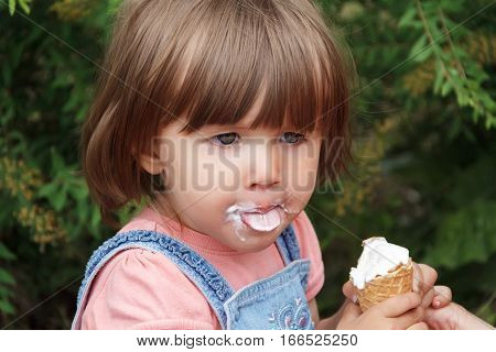 Cute baby girl are eating icecream in summer with put out tongue