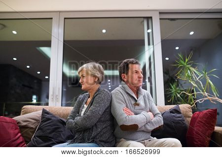 Offended senior woman and man sitting on a couch in living room with arms crossed. Angry, disappointed, sad, having quarrel.