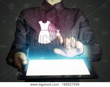 Concept of online shopping service of choice of style. Person (woman) touches to the dress icon. She holds tablet pc that contains a many different online services.