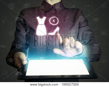 Concept of online shopping service of choice of style. Person (woman) touches to the set of icon: dress jewelry and shoe. She holds tablet pc that contains a many different online services.
