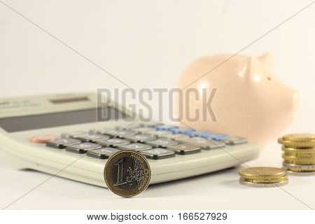 Calculator pen euro coins and piggy bank money box on a light background