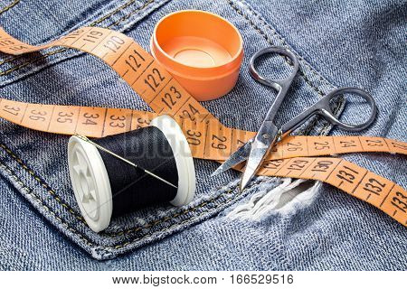 Spool of black thread with a needle tailor's tape measure and scissors on a background of denim
