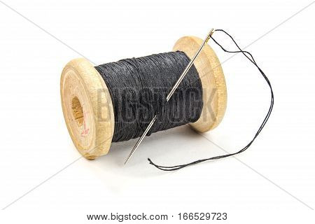 Vintage wooden spool of black thread and needle on white background