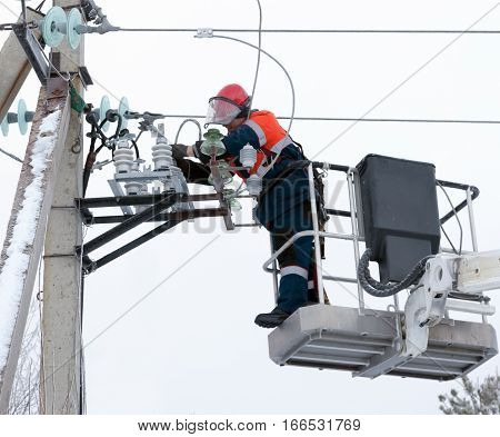 Electrician connect the wires to the line in a special lift vehicles