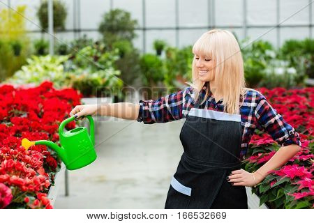 Positive woman gardener watering flowers and smiling. Working in a garden center