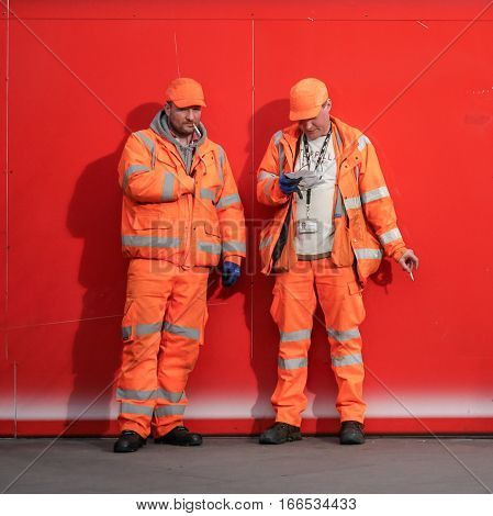 LONDON UK - 25 FEBRUARY 2015: A pair of brightly dressed construction workers taking a cigarette break from their work.