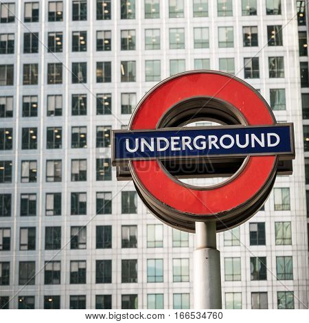 LONDON UK - 13 MAY 2015: The familiar London Underground tube sign (Roundel) set against the windows of the London Docklands skyscraper Canary Wharf tower in the background.