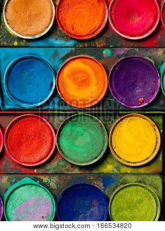 Photo of a palette of watercolor paints and well-used tray.
