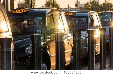 LONDON UK - 13 MAY 2015: A dusk scene of a row of familiar London black taxi cabs lined up at a taxi rank waiting for passengers in Docklands London's business and finance district.