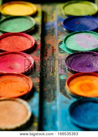 Photo of a palette of watercolor paints on a well-used tray.