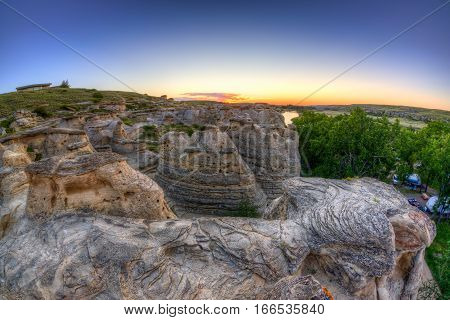 Golden sunrise over the Hoodoo badlands at Writing-on-Stone Provincial Park campgrounds in Alberta Canada. The area contains the largest concentration of First Nation petroglyphs (rock carvings) and pictographs (rock paintings).
