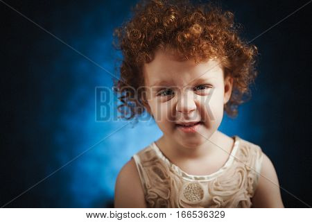 Smiling redhead little girl, with funny face. Cute child with expression on her face.