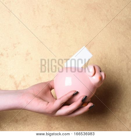 pink piggy bank or moneybox with paper in female hand on beige textured background as savings symbol copy space