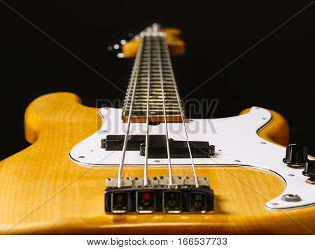 Photo of a electric bass guitar showing perspective from bottom to the headstock. Focus across middle.