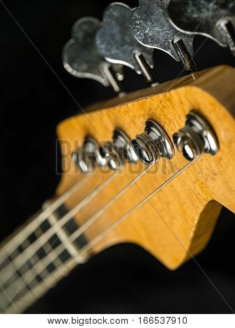 Photo of a bass guitar headstock over black background.