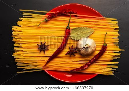 Cooking Pasta With Chili, Garlic And Badian On Red Plate