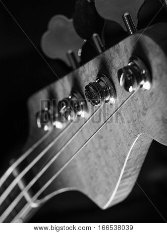 Black and white photo of a bass guitar headstock over black background.