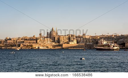 VALLETTA MALTA - 5 FEBRUARY 2016: A view of the city skyline of the ancient capital of Malta Valletta with a Supreme Cruises ferry taking tourists to the old town.