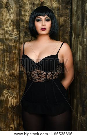 pretty cute young stylish brunette woman in sexy lace corset or underwear on plump body in black wig with red lips posing on brown vintage studio background