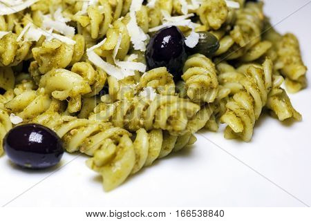 Fusilli topped with pesto sauce black olives and capers. Meal ready to eat
