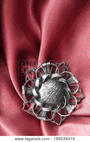 Vintage silver brooch on red draped satin closeup
