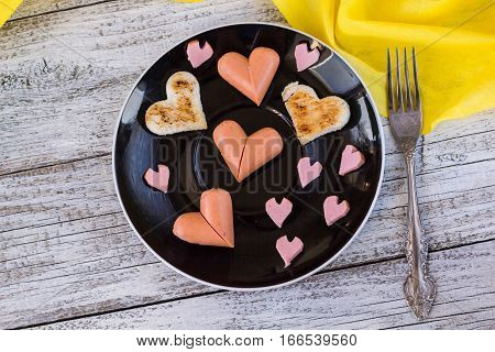 breakfast for the celebration of Valentine's day - toast in the form of hearts sausages in a plate and a fork