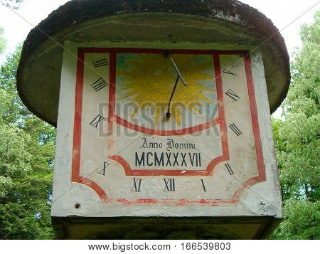 Photo of an old sundial surrounded by greenery