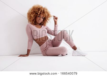 Black Woman Sits On The Floor And Touch A Part Of Her Blonde Hair
