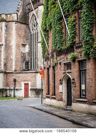 BRUGES BELGIUM - 20 JUNE 2016: A cobbled side street in the Belgian town of Bruges with its red brick architecture including the ivy covered Hotel de Castillion.