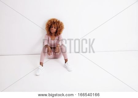 Bblack Blonde Woman Sits On The Floor In White Room
