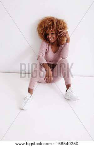 Sport Style Black Woman With Blonde Big Afro Hair Sits On The Floor