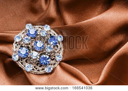 Vintage sapphire golden brooch on crumpled satin closeup