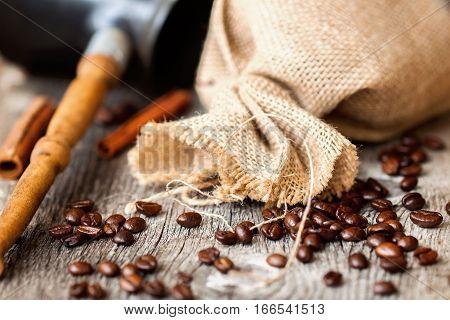 Roasted coffee beans, burlap sac, Cezve, rustic wooden table, cinnamon. Vintage background . Top view grunge texture