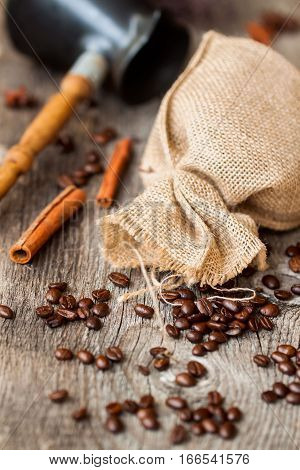 Roasted coffee beans with burlap sac, Cezve, on old weathered wood with cinnamon. Vintage, rustic background use. Lots of place for writing text around it.