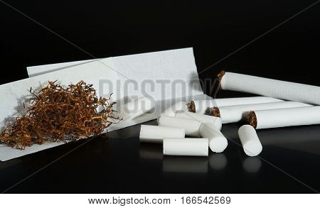 Homemade cigarettes tobacco filters and tobacco paper on black background
