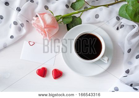 Love background - cup of coffee rose blank love card with free space for love message and two heart shaped candies flat lay of love still life. Top view of love background