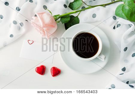 St Valentines day background - cup of coffee rose blank love card and two heart shaped candies. St Valentines day concept of romantic St Valentines day still life. St Valentines day breakfast background
