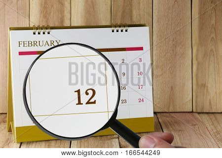 Magnifying glass in hand on calendar you can look twelfth day of monthFocus number twelve in February Concept in business and meetings.