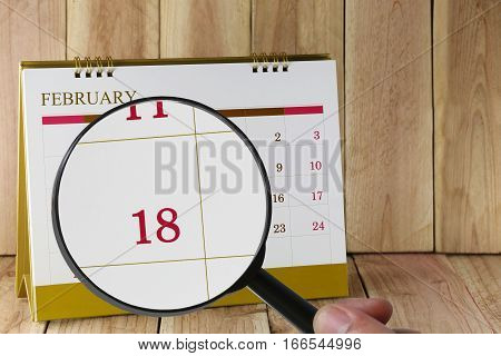 Magnifying glass in hand on calendar you can look Eighteen days of monthFocus number Eighteen in FebruaryConcept in business and meetings.